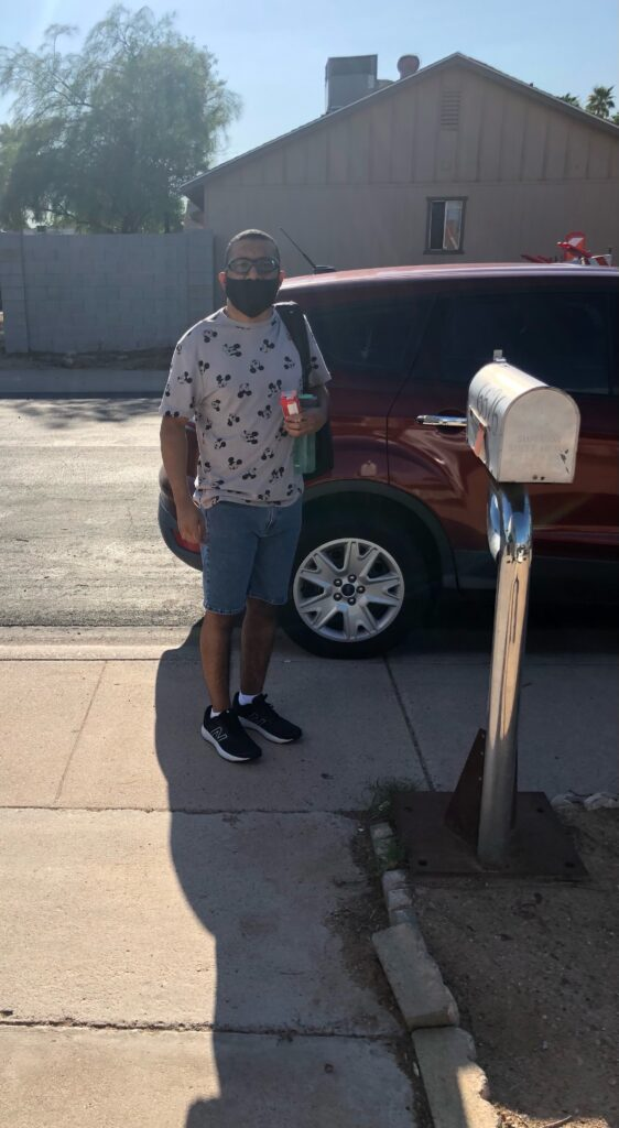 """Photo shows Elijah White, a black teenage male student, wearing a backpack and a mask and standing next to a car on the first day of school. In his backpack is his new AAC device, nicknamed """"Ryan."""" The author encourages all of her clients to nickname their devices and consider them as part of their family- because as their voice, they should go everywhere and do everything with their owner! Other clients have nicknamed their devices """"Big Words,"""" and """"Buttons."""" Is there a new AAC device in your student's backpacks this school year? Or do you need to know how to help your student get one? Tune in to the ArSHA AAC Webinar on August 21st to find out more."""